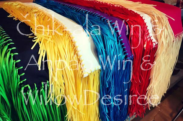 Colorful fringed fancy shawls draped on a table.
